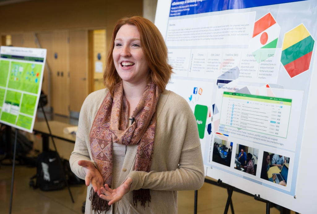 Young woman standing before her research poster.