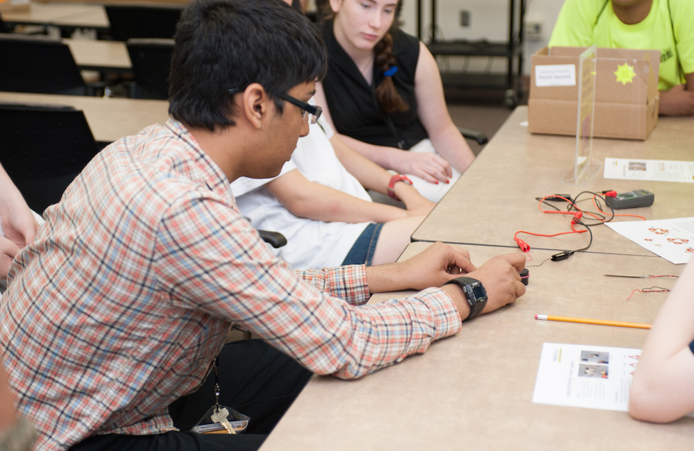 Students gathered around a table in class working on a prototype.