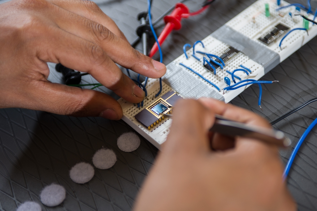 Close-up shot of someone working on a circuit board.