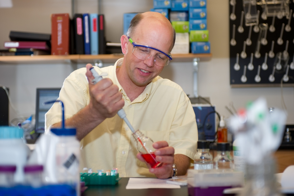 Faculty member pipetting a liquid into a beaker.