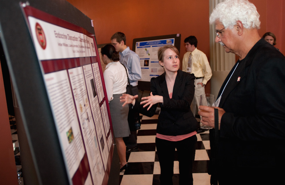 A student presenting her research poster to faculty.