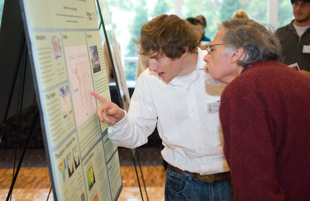 Student and GT faculty member looking closely at a research poster.
